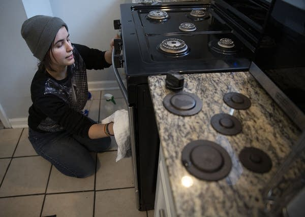 A person kneels on the floor while cleaning an oven door.