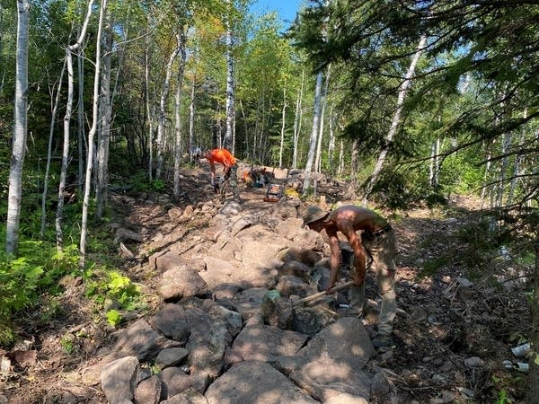 Two people build a mountain bike trail.
