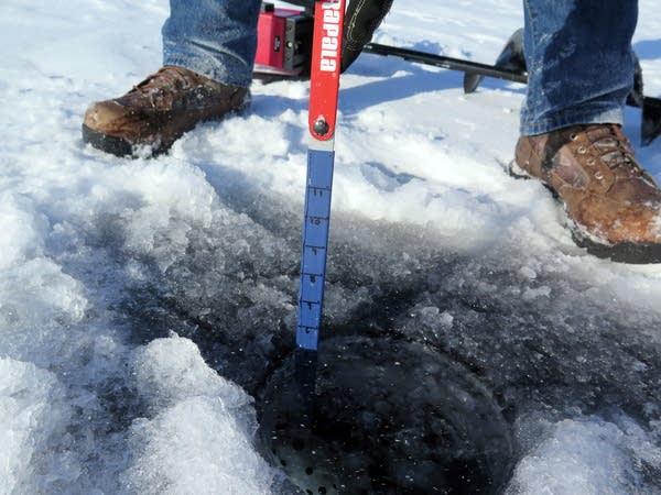Dan Jasper measures the ice thickness.