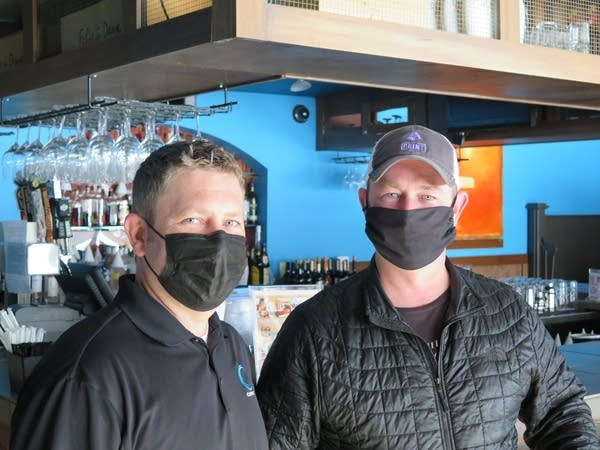 Two men stand in a restaurant with facemasks.
