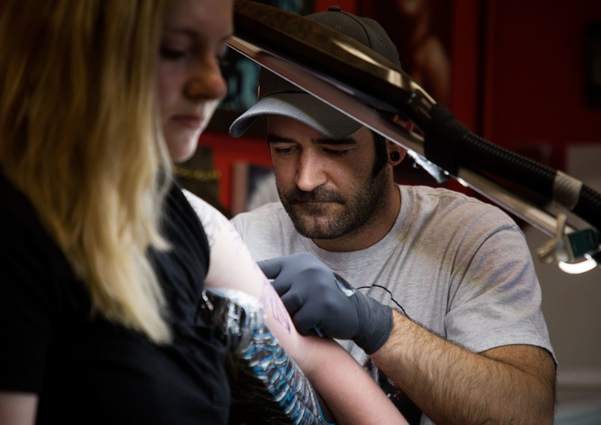 Jason Routley works on a new tattoo for Tailyn Bennett