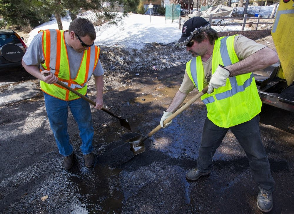 Duluth maintenance workers fill a pothole.