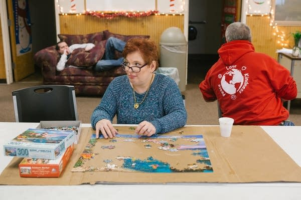 Pauline puts together a puzzle at her day program.