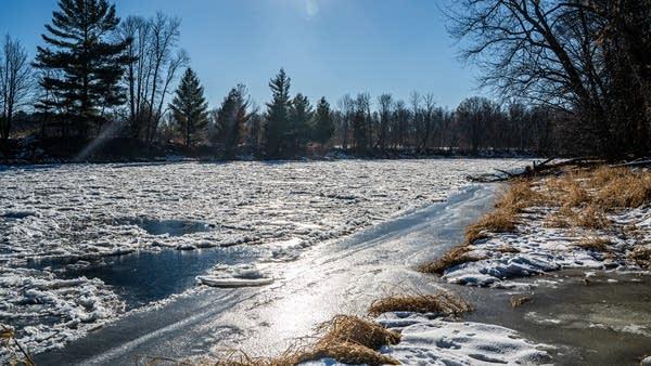 Trees line a frozen river.