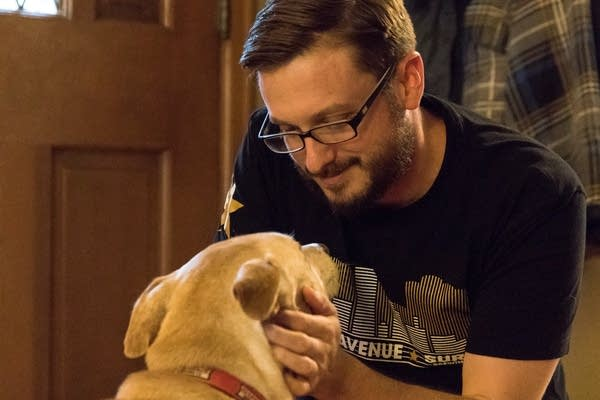 Mike Liay pets his dog Archie in his living room in Northeast Minneapolis.