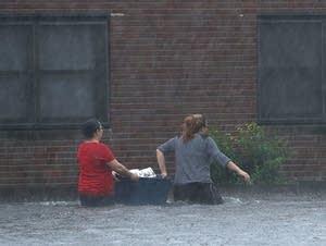 Residents wade through deep floodwater to retrieve belongings