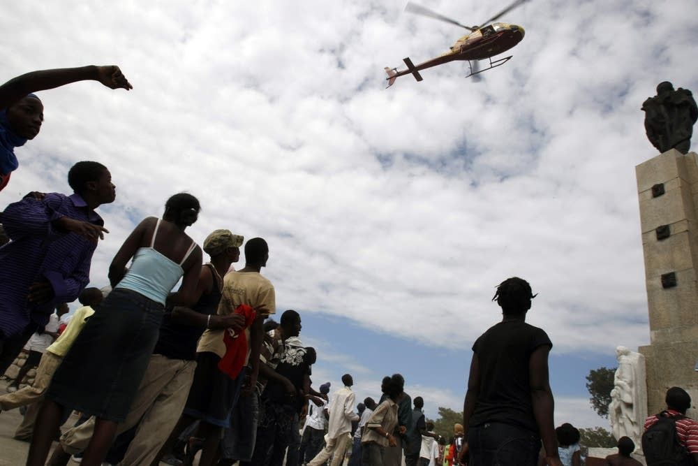 Earthquake survivors wave to a helicopter