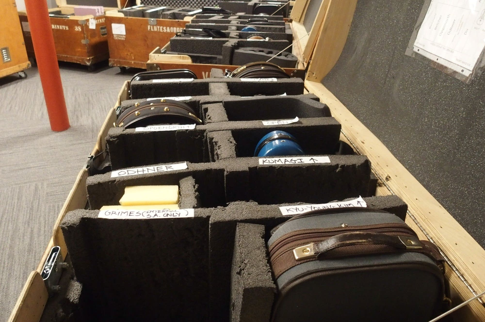 Tour cases filled with violins await the instruments' owners.