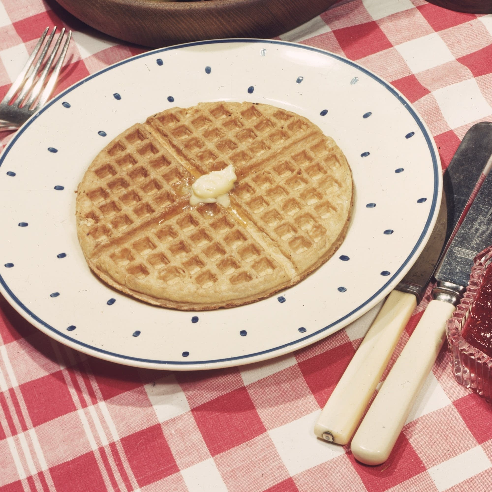 A plate of buttered waffles made in an Easywork waffle iron.