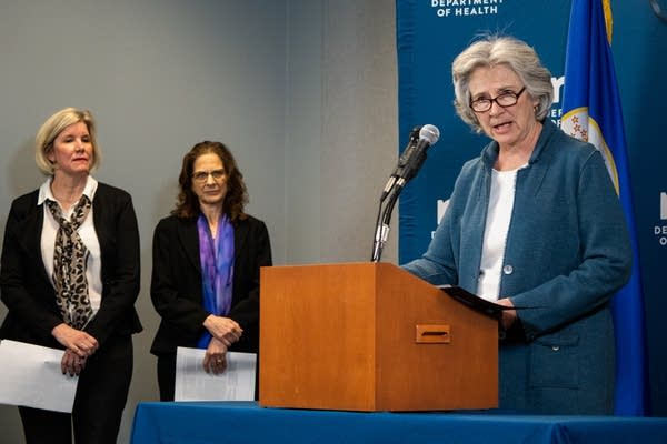 A woman speaks at a podium as two others stand behind her.