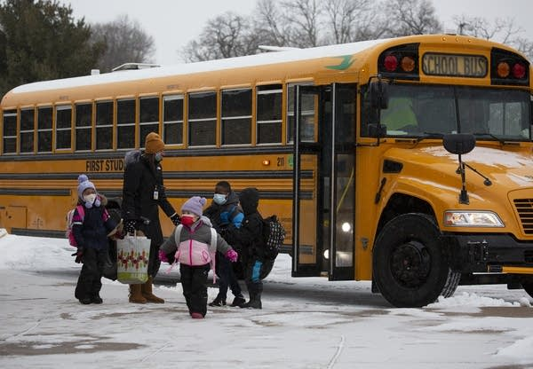 Kids wearing face masks exit a school bus.