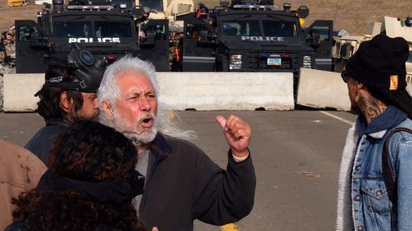 Elder Miles Allard implores protesters to retreat.