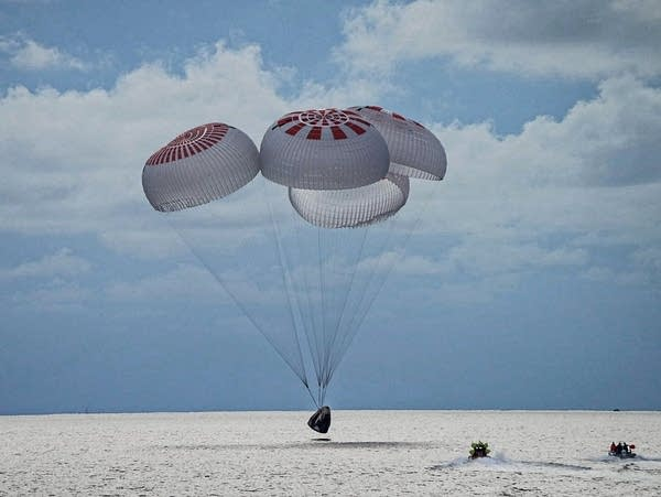 A capsule carrying four people parachutes into the Atlantic Ocean