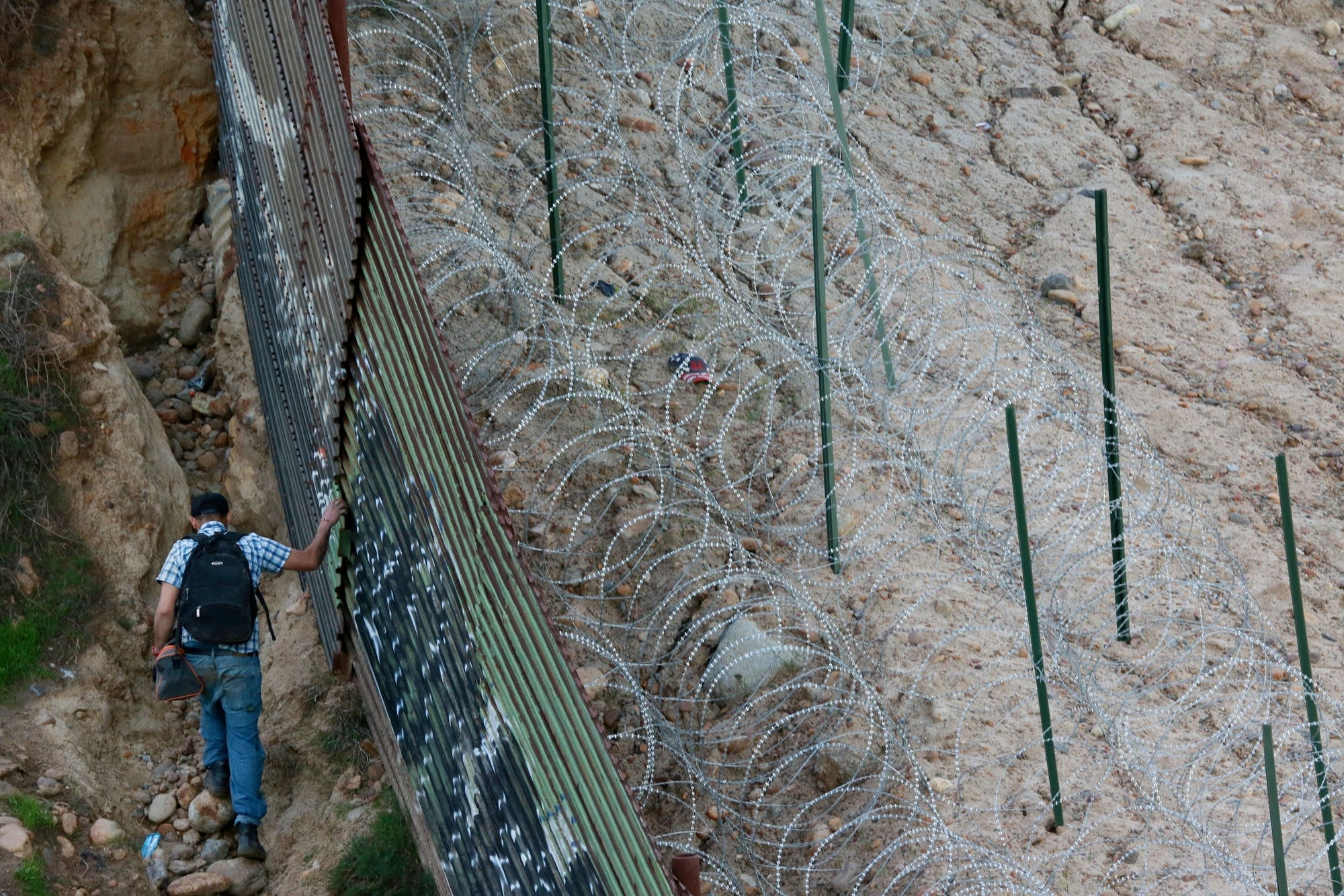 A man walks along the U.S.-Mexico border wall.