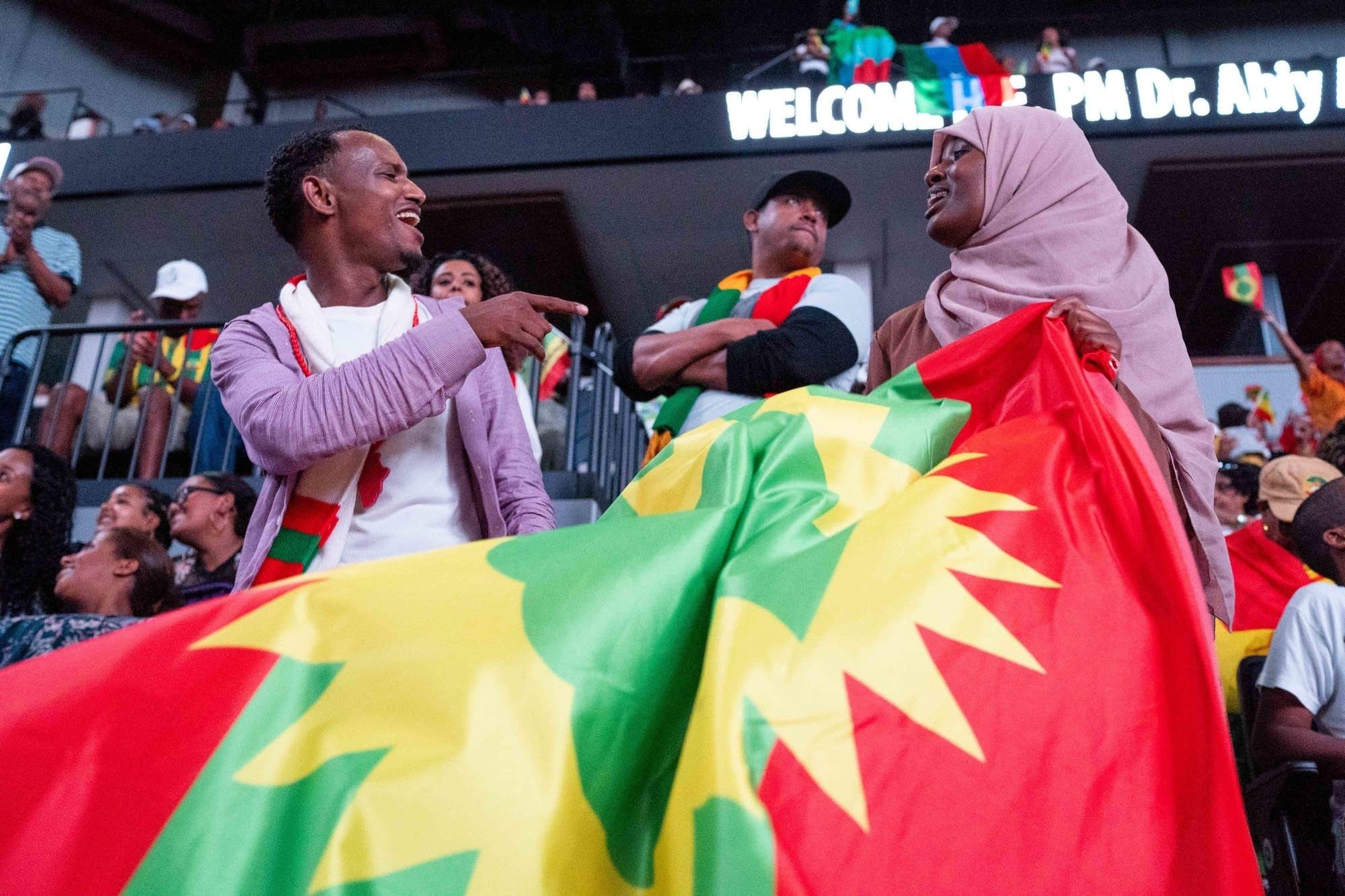 Two attendees dance with the flag of the Oromo people.