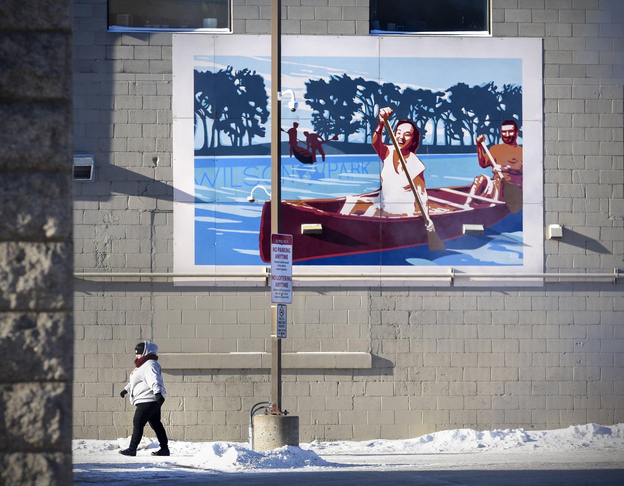 A woman walks past a mural in downtown St. Cloud, Minn.