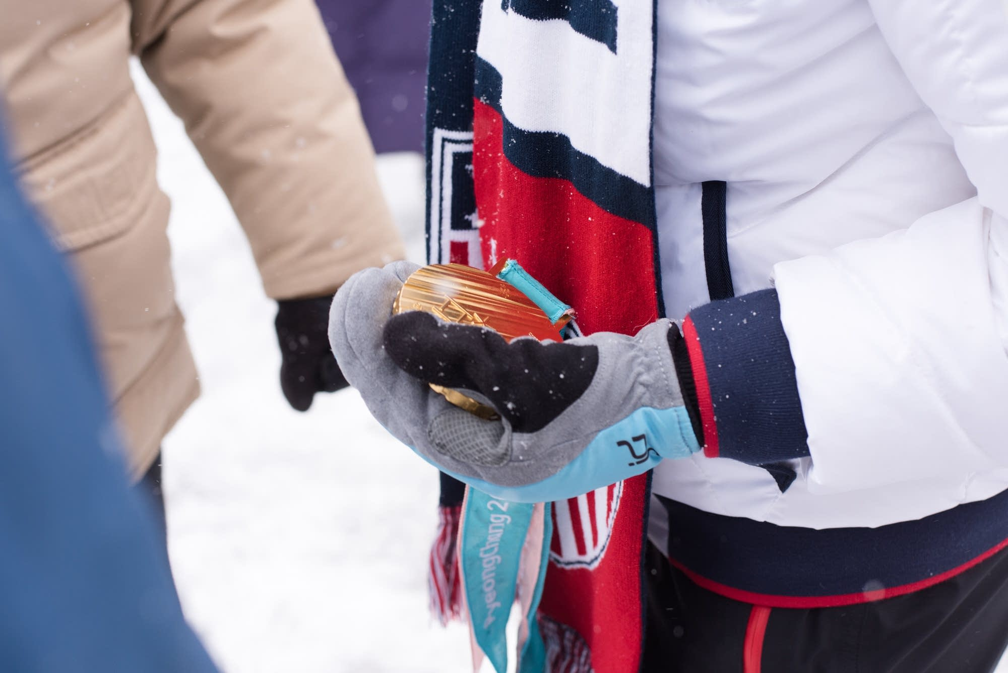 Jessie Diggins holds her gold medal before the start of the parade.