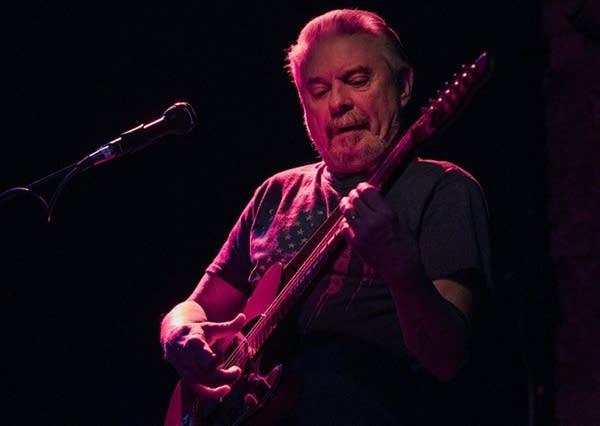A man plays a guitar.