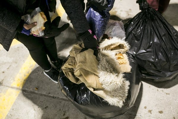 Nakehia Cotton and others grab bags of coats and other possessions