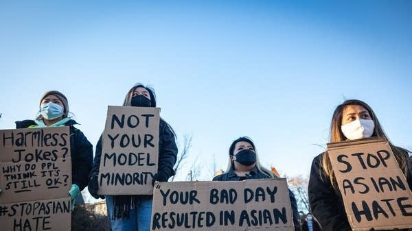 Four people wearing masks hold signs with #StopAsianHate