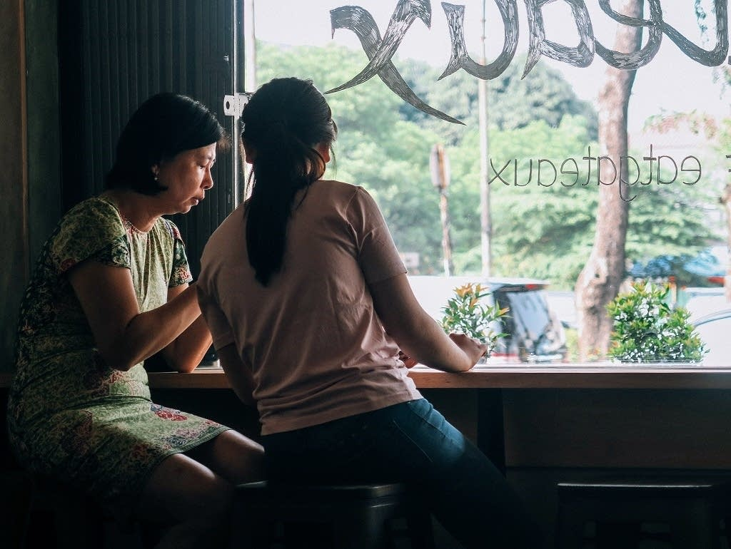 Two women speaking in a cafe