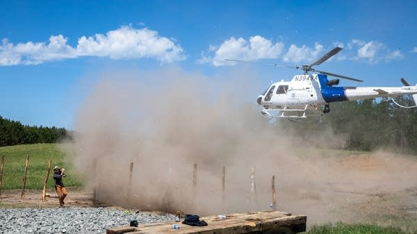 A helicopter stirs up dust and dirt in the air.