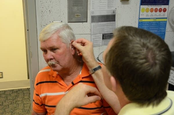 A doctor fits a man for his new hearing aid.