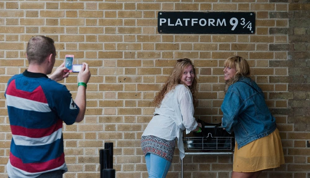 Tourists pose at Platform 9 3/4