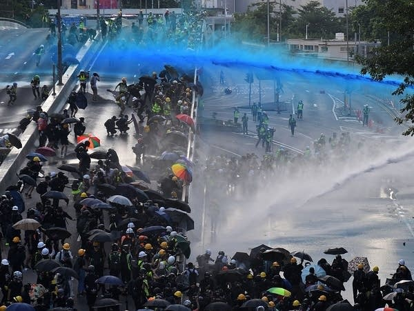 Pro-democracy protesters react as police fire water cannons