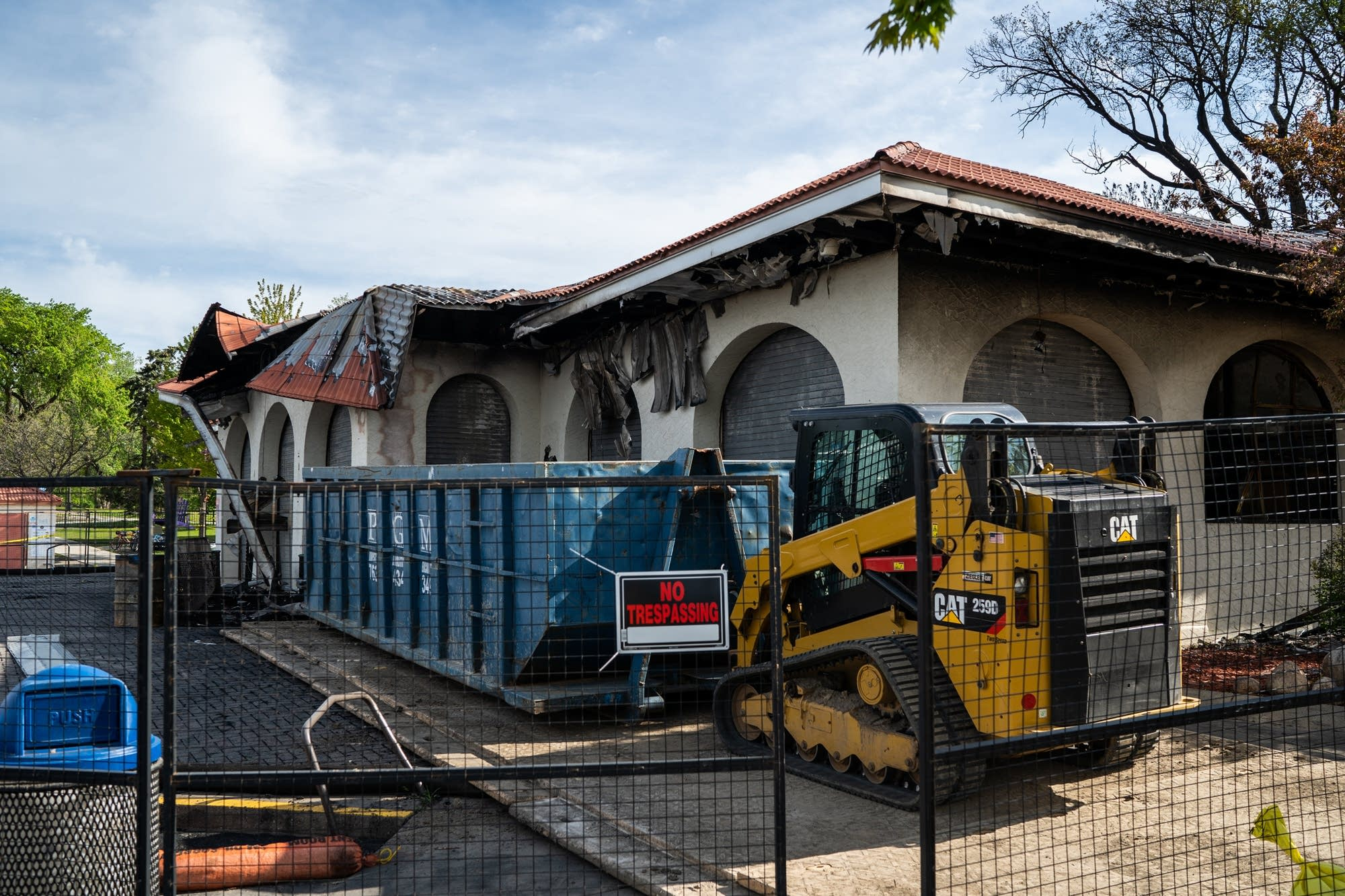 A dumpster and construction equipment sit outside the burned pavilion.