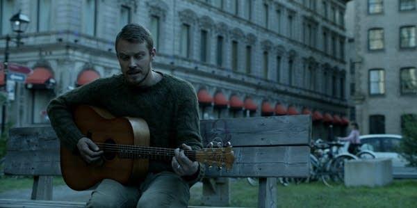 Screen shot from Amazon's Patriot showing John playing guitar
