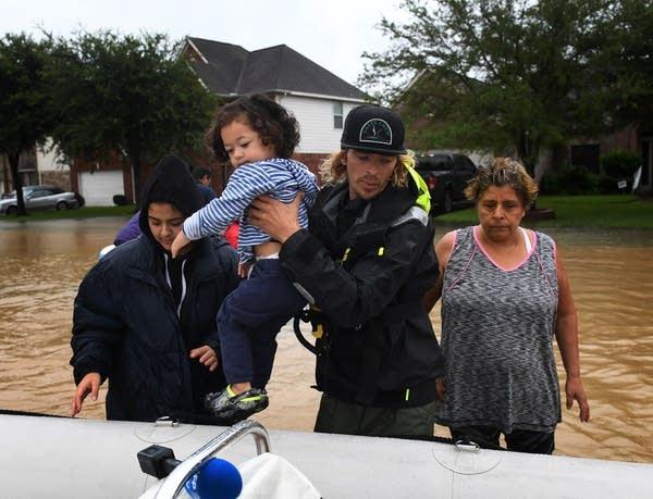 Andrew Brennan helps evacuate an elderly woman and her granddaughter.