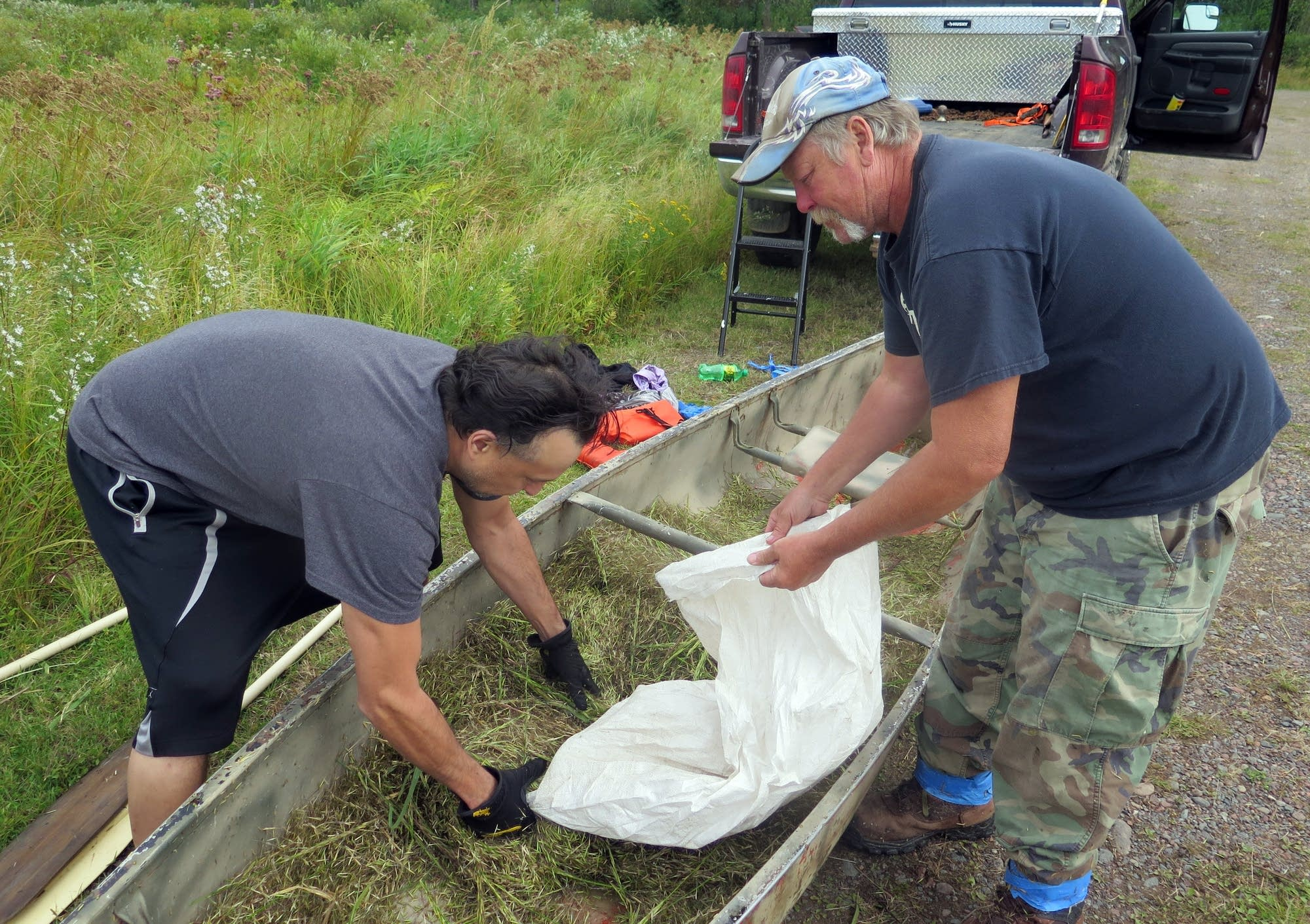 Jerrad Ojibway and Ed Jaakola bag about 80 pounds of wild rice.