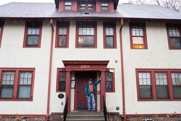 Bob Bono stands on the front step of a rooming house.
