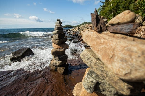 Stones are balanced on top of each other along the lakeshore.