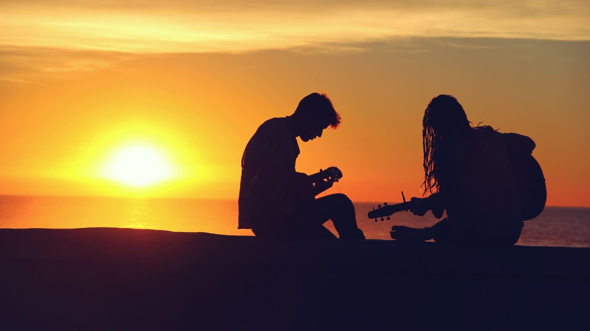 People playing guitar at sunset