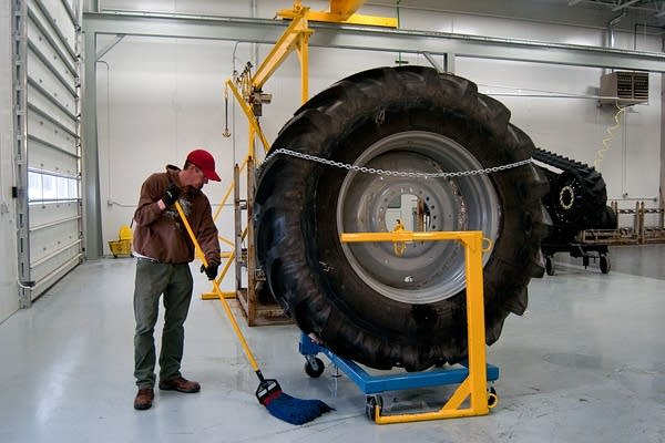 Jasen White mops up around a large tractor tire