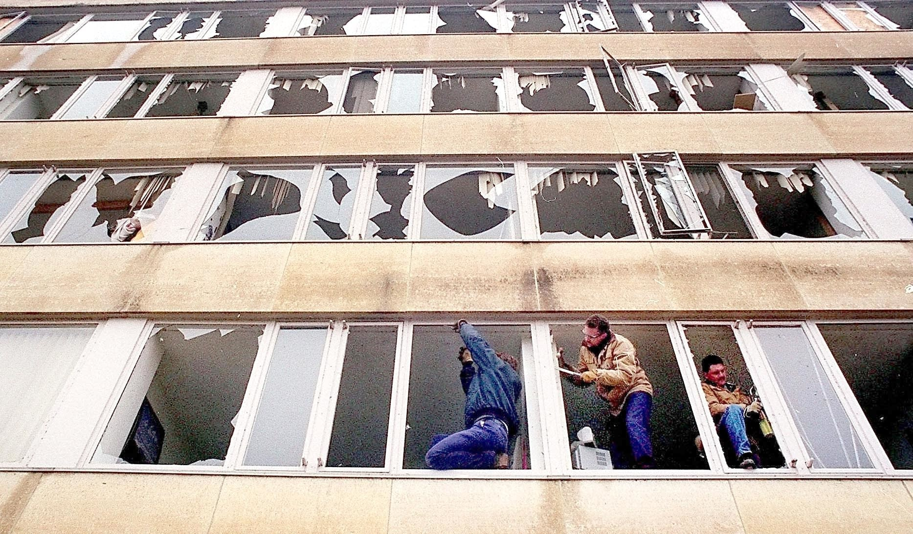 Workers remove broken glass in a Gustavus Adolphus residence hall.