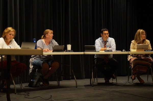 Three women and a man sit at desks on a stage.