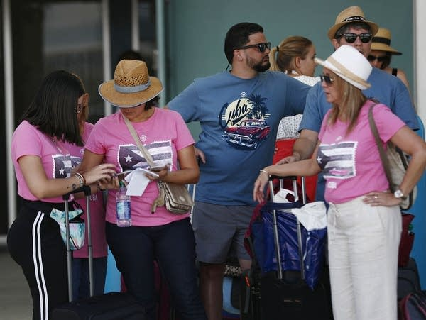Passengers wait for transportation after returning from a cruise to Cuba.