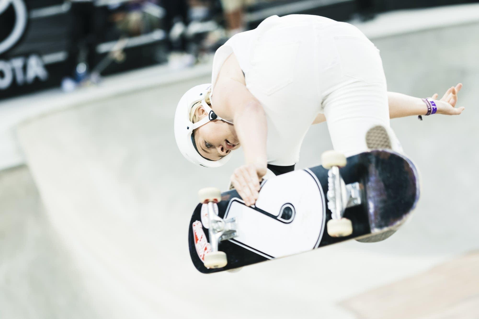Australian Poppy Olsen grabs her board in the air.