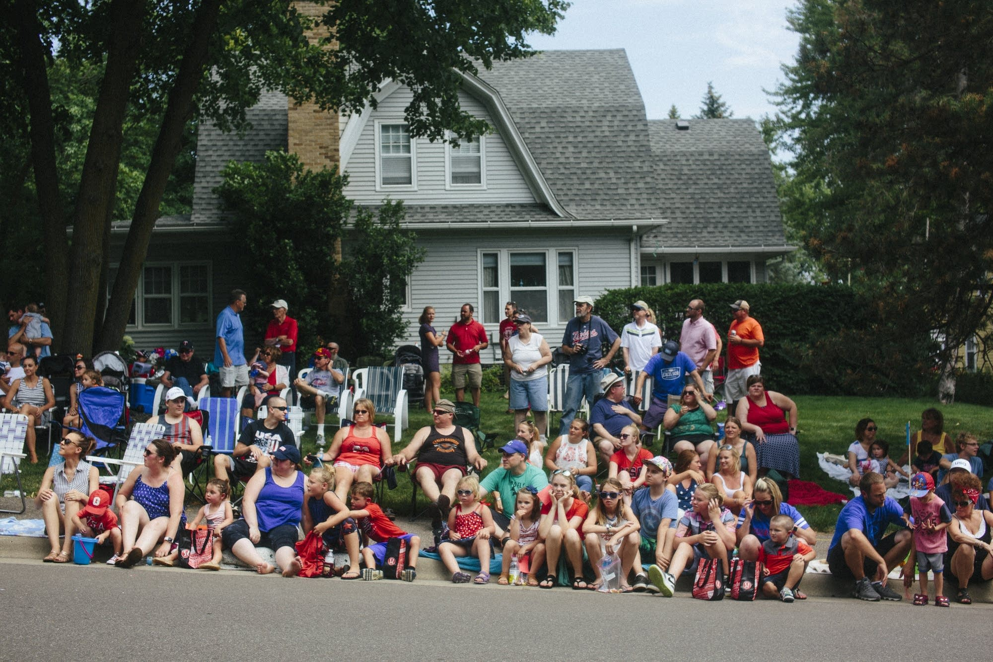 Parade-goers watch floats pass by.