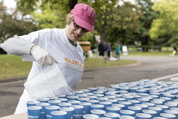 Rebecca Eilers readies water cups for passing runners on Sunday.