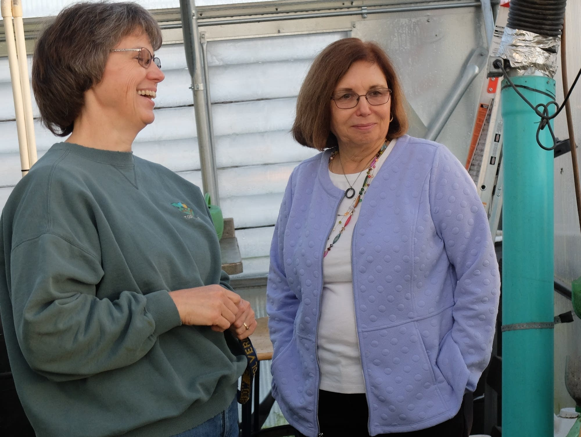 Caroline Venis and Sandie Rentz share a laugh in the greenhouse.