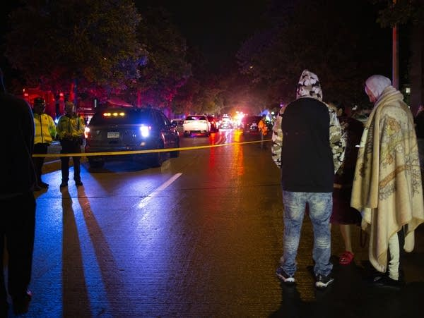 Bystanders watch investigators work at the scene of a police shooting