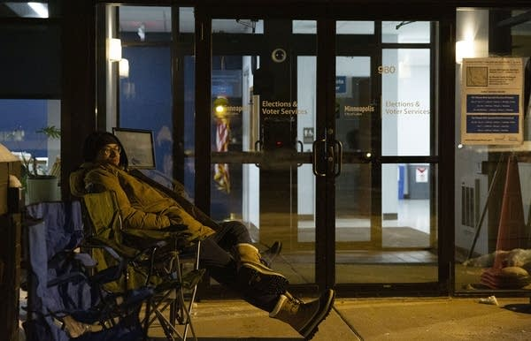 A person sits in a camping chair outside a building