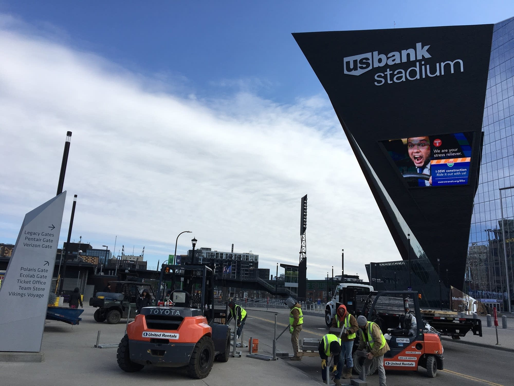 Workers across the street from U.S. Bank Stadium install chain link fence.