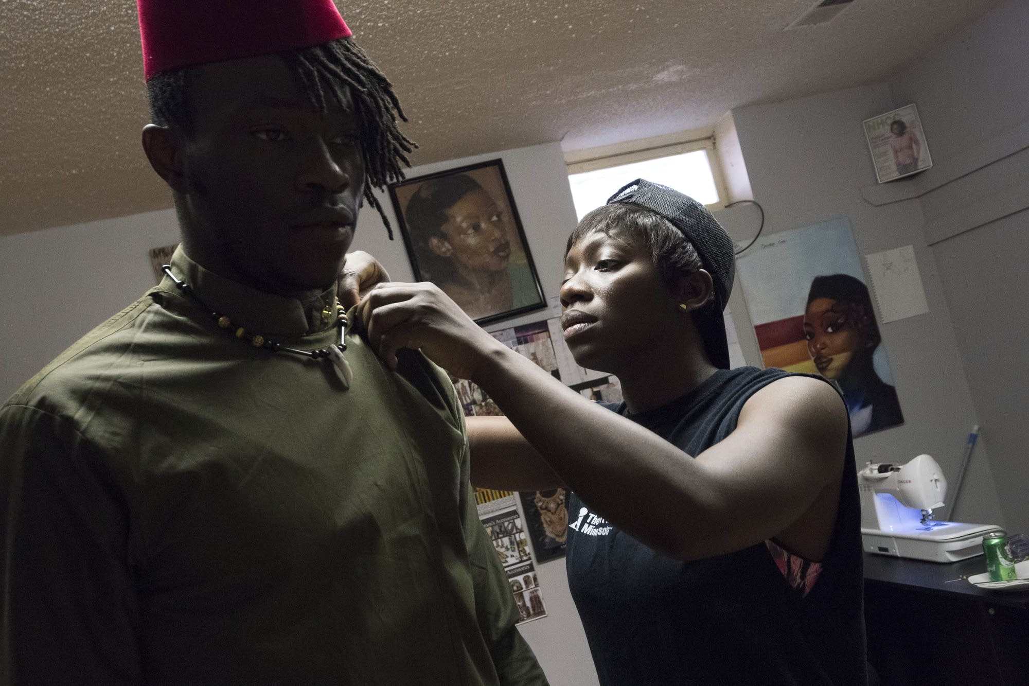 Designer Jacqueline Addison, right, secures a tunic on model Moise Damey.
