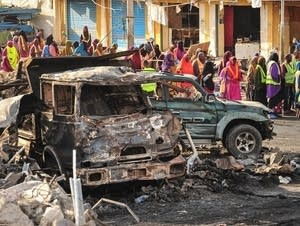 People gather near burned vehicles.