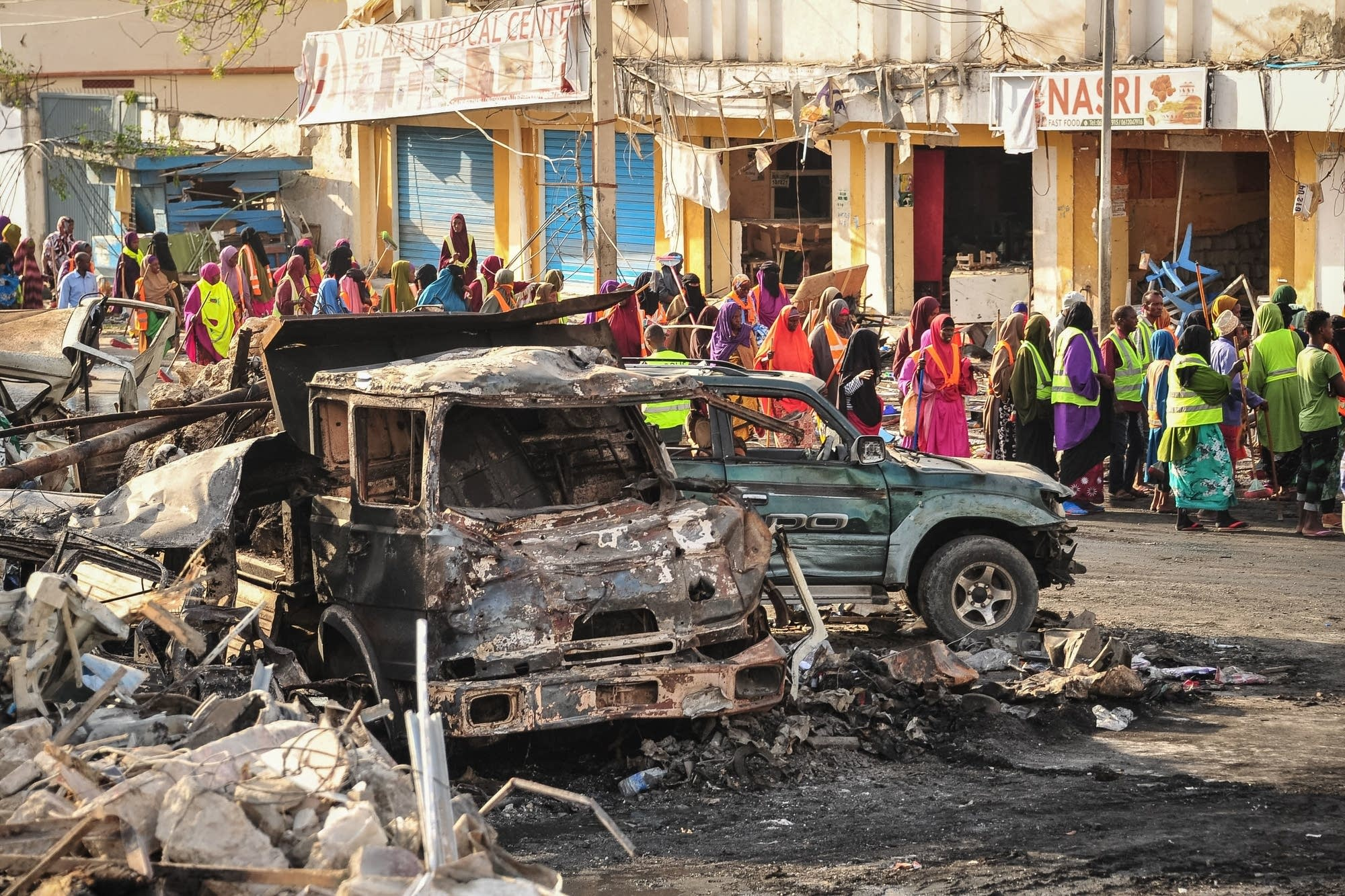 People gather near burned vehicles.